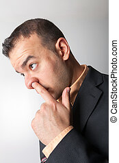 Nose Picker  - Business man sneaking his finger up his nose.