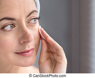 Woman in her forties removing make up - Mature lady using a...