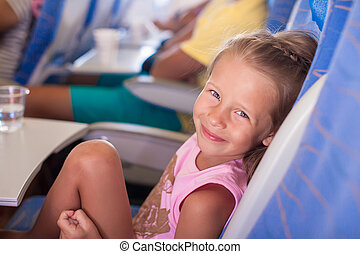 Little smiling happy girl in the airplane