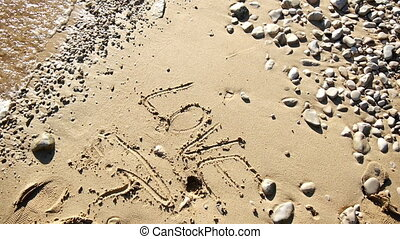 Love word on sandy beach - Word love written on sandy beach...