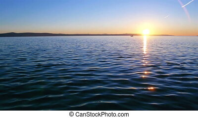 Peaceful scene of sunset on calm blue sea with fishermans in...