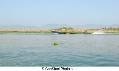 Boat with local peasant goes on Inle lake