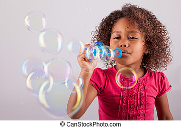 Little African Asian girl blowing soap bubbles - Cute little...
