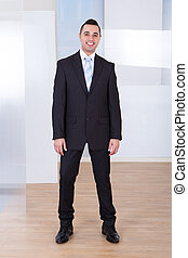 Happy Businessman Standing In Office