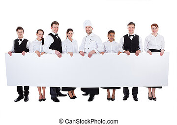 Group of catering staff holding a blank banner - Large group...