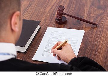 Judge Signing Document In Courtroom - Cropped image of judge...
