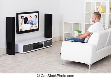 Man sitting on a sofa in his living room watching television...
