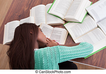 Female student sleeping with books at classroom desk - High...