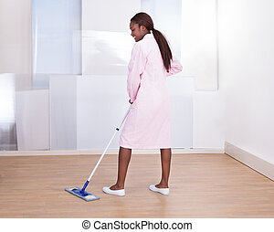 Housekeeper Mopping Floor In Hotel - Full length of female...