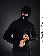 Robber holding a gold bullion bar - Robber disguised in a...