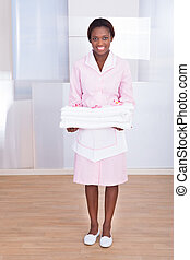Housekeeper Carrying Towels In Hotel - Smiling young female...