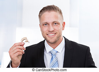 Businessman holding hearing aid - Photo of the businessman...