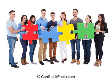 Group of people connecting puzzle pieces over white...