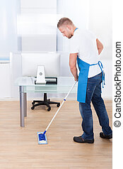 Janitor cleaning the floor in an office building - Handsome...