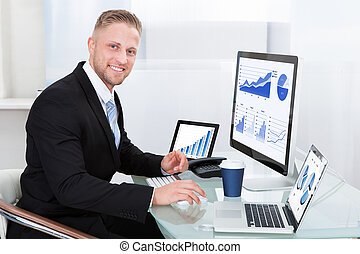 Businessman with good performance graph sitting at his desk...