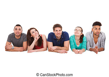 College Students Lying Over White Background - Portrait of...