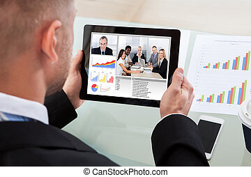 Businessman on a video or conference call on his tablet with...