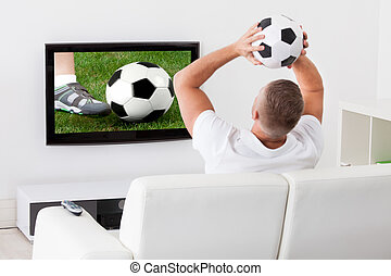 Soccer fan watching a game on television holding a soccer ball