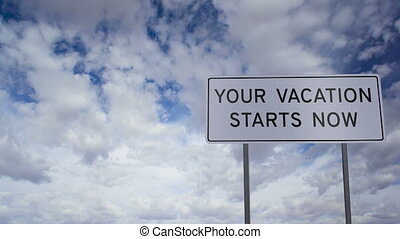 Sign Vacation Now Clouds Timelapse - Road sign with the...