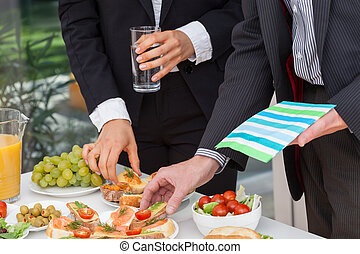 Business people eating lunch at office buffet