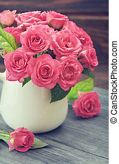 Bouquet of pink roses in vase on wooden background