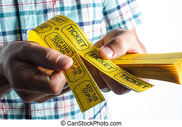 Raffle tickets - A person holding a stack of raffle tickets.