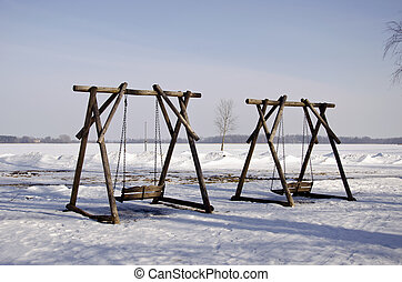 two wooden swings in winter park - two wooden empty swings...