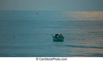 Sea fishing - Two fishers in round fishing boat at the sea