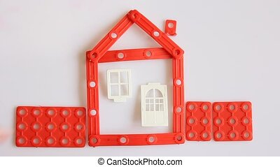 Human hand builds red house on white background