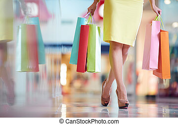 Leaving the mall - Legs of shopaholic with shopping bags...
