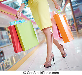 Consumerism - Legs of shopaholic with shopping bags walking...