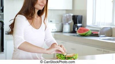 Pretty woman making a sandwich