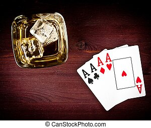 top of view of poker playing cards near wiskey glass on old...