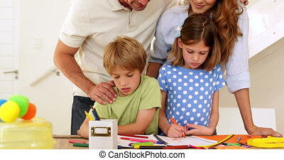 Happy parents and children drawing together looking at...