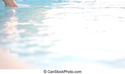 Woman splashing feet in the pool