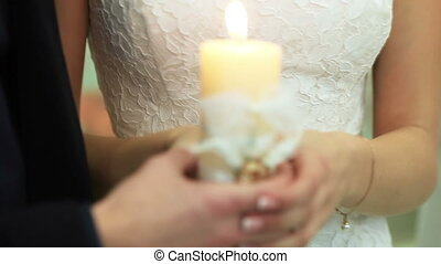 Wedding candle - Bride and groom are holding a burning...
