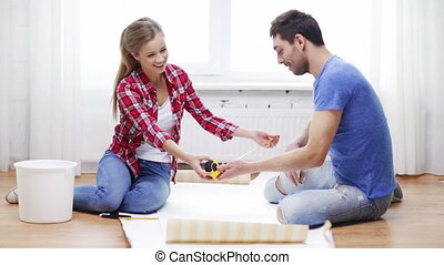 smiling couple measuring wallpaper - repair, building and...