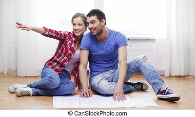 smiling couple discussin blueprint at home - repair,...