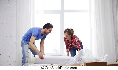 smiling couple opening big cardboard box with sofa - repair,...