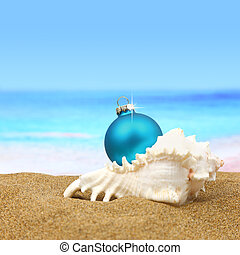 Christmas ball in a sea shell on the beach