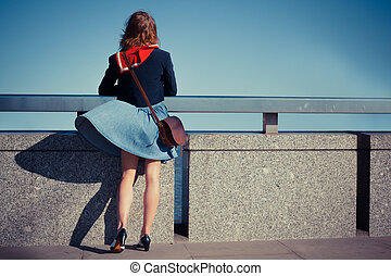 Young woman standing on bridge with her skirt blowing - A...