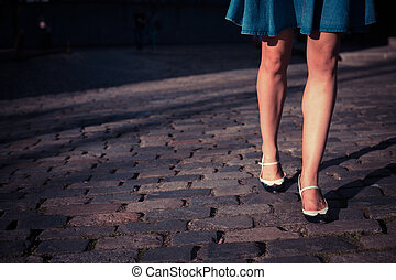Young woman in skirt walking on a cobbled street - A young...
