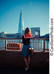 Young woman admiring the Shard in London - A young woman is...