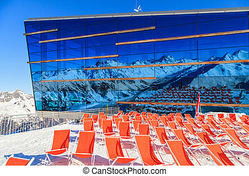 Mountain deckchairs - Deckchairs and mountains reflected on...