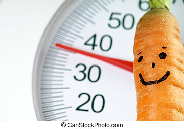healthy eating - Carrot with face on a Body Scales