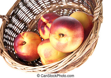 nectarines - Nectarines in a basket isolated over a white...