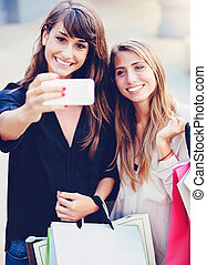 """Beautiful girls with shopping bags taking a """"selfie"""" with..."""