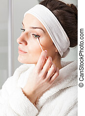 Woman removing make-up - Woman in white bathrobe removing...