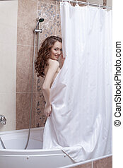 Shy smiling woman posing nude in shower