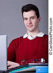 Man using laptop - Young man using his laptop at work